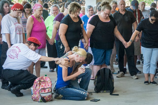 Sarah Lewis is comforted by Danny Noggle III and a member of the Bucyrus Guardian Angels as prayers are said as family members, friends and officials gathered on the steps of the Bucyrus City Hall in September 2014 to remember the four men who were killed in the city.