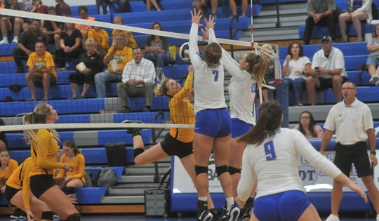 Colonel Crawford's Jenna Maddy tries to lift the ball over the outstretched arms of Wynford's Lainey Holman and Lyndie Williams at the net.