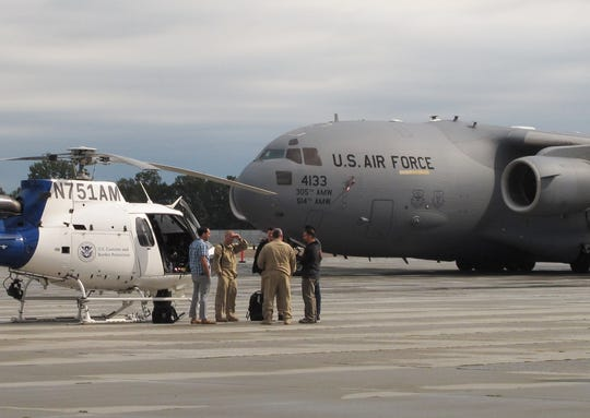 Officials with the Department of Homeland Security confer at Burlington International Airport in advance of Vice President Mike Pence's visit on Friday, Aug. 30, 2019. The U.S. Air Force transport plane, laden with the vice president's gear, arrived earlier.