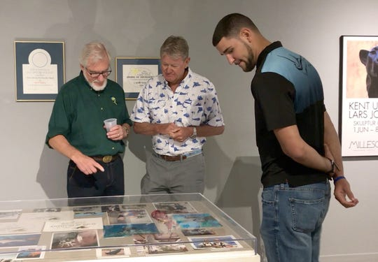 "Kent Ullberg (left) and Guy Harvey (center) view images from dives the two artists have colloborated on as Harvey's son and marketing director, Alex Harvey (right), looks on at the Art Museum of South Texas May 24, 2019. Harvey was in Corpus Christi to view Ullberg's exhibit, ""Celebrating the Wild and Wonderful."""