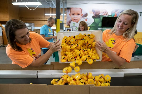 "Autumn Beavers, left, and Olivia Klatwitter dump ""tagged"" ducks onto a conveyor belt in preparation for the 25th Annual Rubber Duck Regatta on Friday, Aug. 30, 2019 at the Freestore Foodbank in Bond Hill, Ohio. The numbers will identify the owners of the winning ducks on September 1st regatta on the Ohio River."
