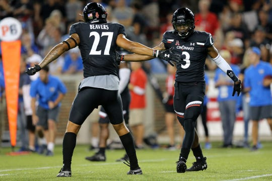 Cincinnati Bearcats safety Ja'von Hicks (3) and Cincinnati Bearcats safety Will Adams (27) high five after a defensive stop in the fourth quarter of an NCAA football game, Thursday, Aug. 29, 2019, at Nippert Stadium in Cincinnati. Cincinnati won 24-14.