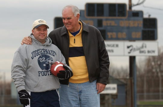 In this photo taken Nov. 26, 2003, Lloyd High School football coach Roy Lucas Jr., left, gets a hug from his father, Roy Sr.