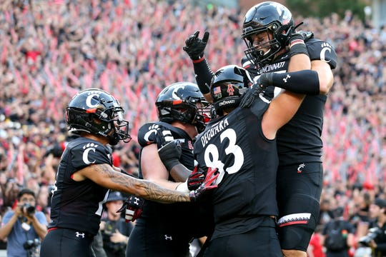Cincinnati Bearcats tight end Josiah Deguara (83) is congratulated after scoring a touchdown in the second quarter of an NCAA football game against the UCLA Bruins, Thursday, Aug. 29, 2019, at Nippert Stadium in Cincinnati.