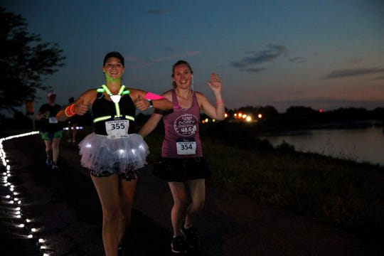 Runners have fun at the 2018 Hamilton NightGlow race. Part of the route is along the Great Miami River.