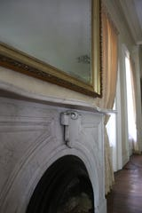 A grand living room in the Robb-Hayes House still shows signs of grandeur, including two marble fireplace mantels.