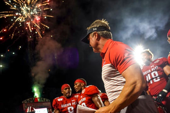 Austin Peay head coach Mark Hudspeth stands with his team in front of fireworks and the band playing fight songs after winning the season opener football game for Austin Peay at Fortera Stadium in Clarksville, Tenn., on Thursday, Aug. 29, 2019.