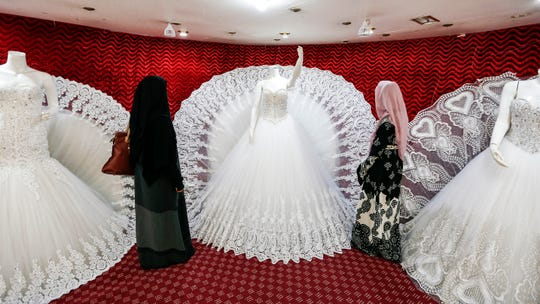 Two Yemeni women browse through wedding dresses in a shop in the capital Sanaa.