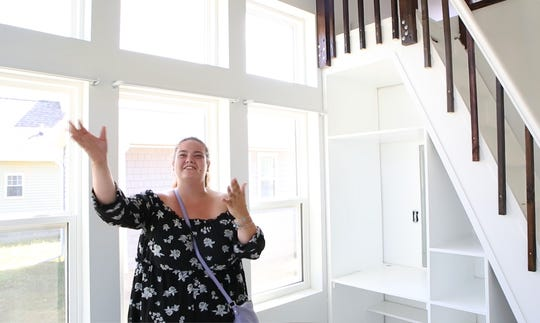 Amanda Funk, 25, a new member of the Cass Community Social Services Tiny Homes neighborhood reacts to seeing her new home for the first time.