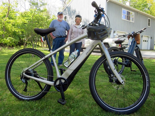 Gordon and Janice Goodwin show their electric-assist bicycles outside their home in Bar Harbor, Maine.