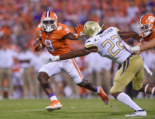 Clemson's Travis Etienne (9) fends off Georgia Tech's Kaleb Oliver to gain a first down during the first half of Thursday's game.