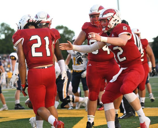 Chippewa Valley quarterback Josh Kulka (12) comes over to celebrate with Antwaine Gunter (21) after Gunter's touchdown in the first half.