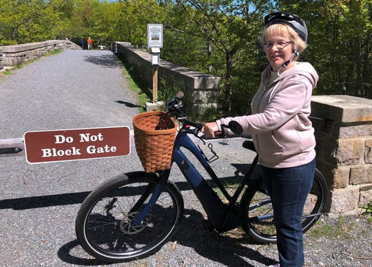 Janice Goodwin stands by her electric-assist bicycle at a gate near the start of the carriage path system inside Acadia National Park on  June 8, 2018, in Bar Harbor, Maine.