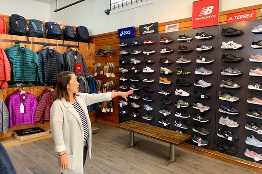 In this photo taken Wednesday, Aug. 28, 2019, Jennifer Lee, whose family owns Footprint shoe story in San Francisco, points to wall of athletic shoes, many of which are made in China and will be subject to new US tariffs on Chinese goods starting Sept 1.
