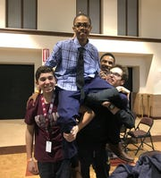 University of Detroit Jesuit High School sophomore Ryan Jones is lifted by his teammates in celebration after winning an esports tournament.