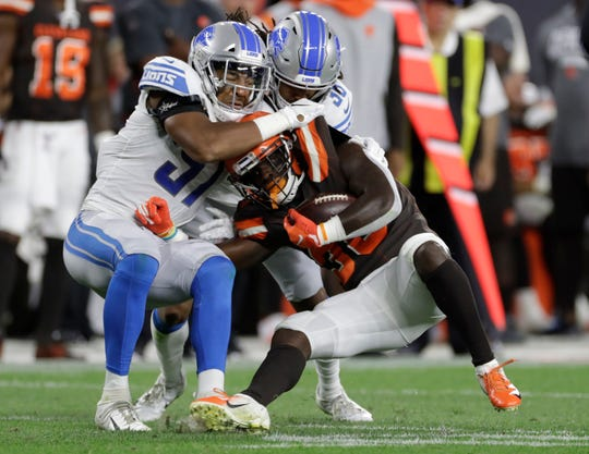 Lions linebacker Anthony Pittman (57) helps tackle Browns running back D'Ernest Johnson (30) earlier this year.