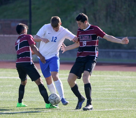 Ian Aepelbacher of Horseheads tries to split Elmira players Michael Taylor (7) and Noah Sperduto (19) during the Express' 2-0 boys soccer win Aug. 30,  2019 at Ernie Davis Academy.