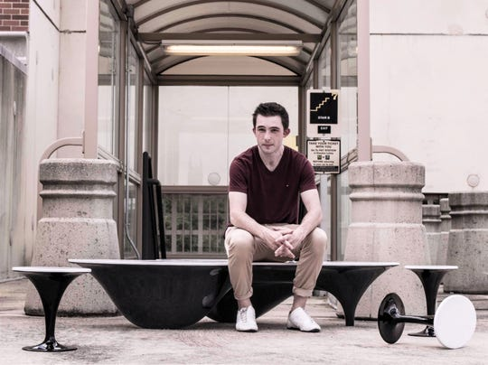 Big Flats native and entrepreneur Samuel Pawlak sits on a high-end coffee table he designed through his business, Livesay Ether.