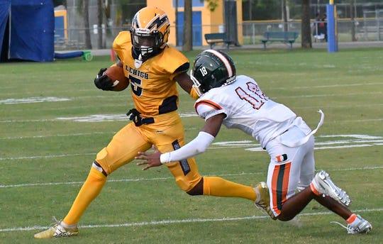 Lehigh High School Tarvarish Dawson (5) runs a ball while trying to fight off Dunbar Tigers defender Alphonso Churchill (18) during their game in Lehigh, Thursday,  Aug. 29, 2019.