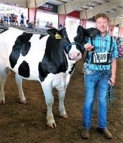 Bradin Bjelland, 13, is seen with his Holstein dairy steer Sherlock at the Wisconsin State Fair this month. Bradin won the breed award for Champion Registered Dairy Steer.