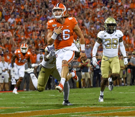 Clemson quarterback Trevor Lawrence (16) scores the first touchdown of the season near Georgia Tech defensive back Ajani Kerr (38) during the first quarter at Memorial Stadium in Clemson Thursday, August 29, 2019.