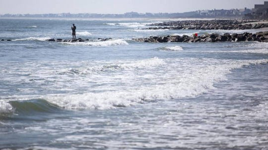A fisherman stands on a rock groin along the South Carolina coast. Groins are supposed to help protect beaches from erosion, but critics say they don't work.