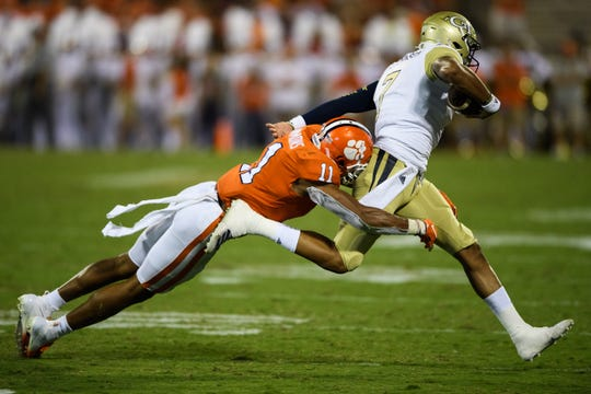 Clemson safety Isaiah Simmons (11) tackles Georgia Tech quarterback Lucas Johnson (7) during their game at Memorial Stadium Thursday, Aug. 29, 2019.