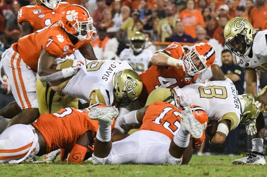 Clemson defensive lineman Tyler Davis(13) tackles Georgia Tech quarterback Tobias Oliver (8) with help from linebacker James Skalski (47), and defensive end K.J. Henry(5) during the second quarter at Memorial Stadium in Clemson Thursday, August 29, 2019.
