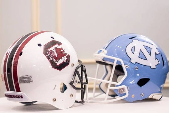 Helmets from the University of South Carolina and University of North Carolina are placed on table during a press conference with Will Muschamp and Mack Brown at the Charlotte Country Club Friday May 10, 2019, in Charlotte, NC. USC and UNC will play against each other in the first game of the season.