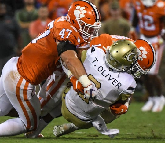 Clemson linebacker James Skalski (47) and safety Isaiah Simmons (11) tackle Georgia Tech quarterback Tobias Oliver (8) during the first quarter at Memorial Stadium in Clemson Thursday, August 29, 2019.