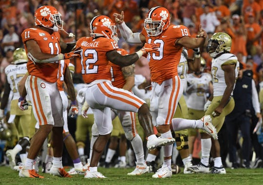Clemson defensive back Tanner Muse (19) celebrates a turnover with safety Isaiah Simmons (11), and defensive back K'Von Wallace (12) during the third quarter at Memorial Stadium in Clemson Thursday, August 29, 2019.