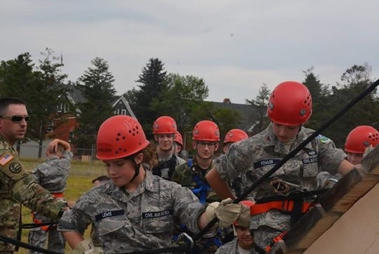 Cadets Danica Lewis and Rose Fowler make it to the end of the rappelling tower.