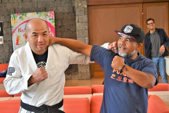 Tetsuji Kato, left, and Roman Dela Cruz ham it up at the Pacific Star Hotel lobby following weigh-ins for the 2019 Marianas Open. Kato is Division 1 black belt competitor, Dela Cruz a sponsor.