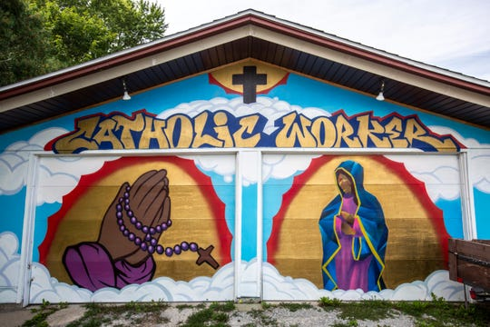 A mural on a garage featuring praying hands and crosses is pictured, Friday, Aug. 30, 2019, at the Catholic Worker House in Iowa City, Iowa.