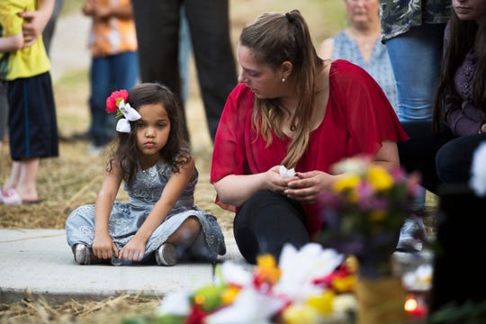 "Bella Pheap, 5, daughter of Channara Tom ""Philly"" Pheap, sits next to her mother, Jessica Beverwyk, while looking at a memorial for her father at an apartment complex in northwest Knoxville on Thursday, Aug. 29, 2019. A Knoxville police officer shot and killed Pheap on Aug. 26."