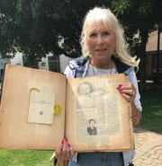 Lancaster Business & Professional Women's Club President-Elect Mona Finnestad shows a recently-discovered scrapbook detailing some of the club's history.