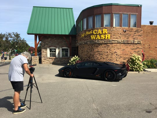 Lindsay Root films a shot of a 2018 Lamborghini Aventador SV owned by Howell resident Art Rimbold. Rimbold loaned the car, worth $500,000, for a commercial shoot on Friday Aug. 30, 2019 at Soft Cloth Car Wash in Howell.