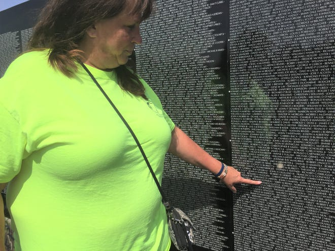 Prisoner of War Committee of MichiganPresident Debbie McClain touches her uncle Roland Pineau's name on the The Vietnam Memorial Moving Wall during its visit to Hamburg Township, Friday, Aug. 30, 2019.