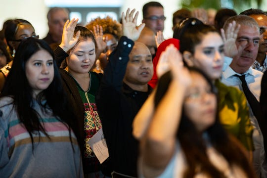New citizens raise their hands as 194 people took the oath of citizenship during a naturalization ceremony at the Muhammad Ali Center. August 30, 2019