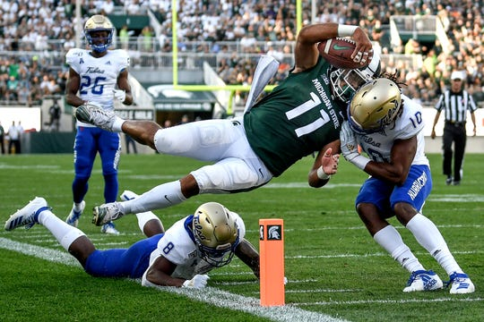 Michigan State's Connor Heyward leaps to scoresa touchdown against Tulsa's Manny Bunch, right, and Brandon Johnson during the first quarter on Friday, August 30, 2019, at Spartan Stadium in East Lansing.