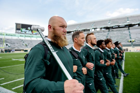 MSU's Mike Panasiuk carries a sledge hammer while participating in the team walk before the Spartans game against Tulsa on Friday in East Lansing.