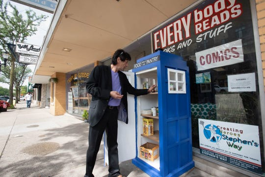 "David Jaramillo of Lansing checks out ""TARDIS,"" the Punks with Lunch food pantry Friday, Aug. 30, 2019, located in front of Everybody Reads bookstore on East Michigan Avenue in Lansing. The pantry resembles the TARDIS time machine from the British adventure show ""Dr. Who.""  People are encouraged to take what they need and leave what they can."
