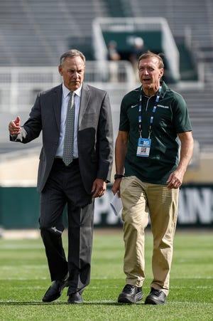 MSU President Samuel Stanley walks with former Spartan football coach Mark Dantonio before last year's season opener.