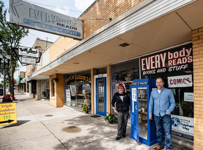 """Punks with Lunch co-founder Julia Miller, pictured Friday, Aug. 30, 2019, alongside James Bignall, right, who built the free food pantry located in front of Everybody Reads bookstore on East Michigan Avenue in Lansing. The pantry resembles the TARDIS time machine from the British adventure show """"Dr. Who."""""""
