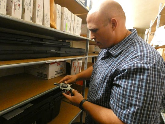 Marion Police Major Jon Shaffer holds a firearm recovered by police and held in evidence at the Marion Police Department.