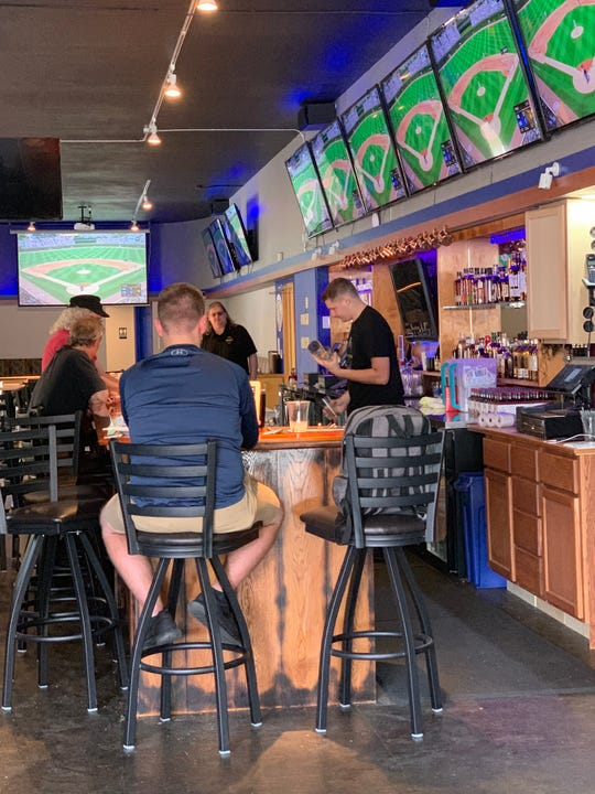 Boomerangs Bar & Grill co-owners Brady Rice, foreground, and John Hintz, stand behind the bar on the restaurant's first day open on Aug. 30. The sports bar includes 13 televisions, with a 14th planned, and serves favorites that include a variety of wings and pizza made from scratch.