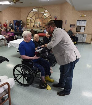 U.S. Rep. Rick Crawford (standing) presents an American flag and a quilt to U.S. Army veteran Phillip Olson on Friday at Gassville Therapy & Living. Crawford recognized nine veterans living at the facility on Friday.