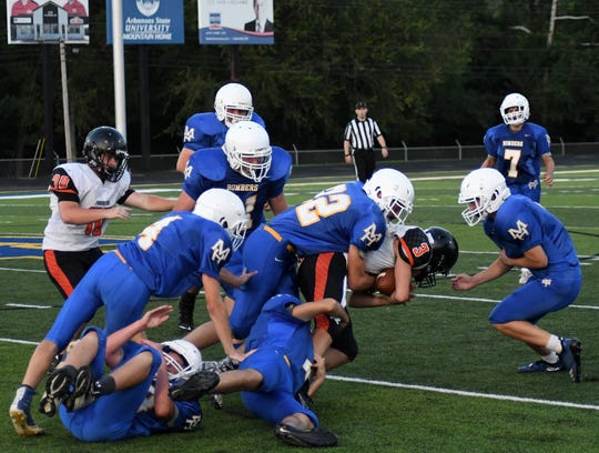 Mountain Home's Dylan McBride (22) leads a squadron of Junior Bombers while bringing down Batesville's Jay Storlie on Thursday night at Bomber Stadium.