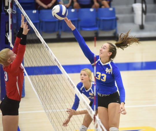 Mountain Home's Anna Grace Foreman (33) hits over Paragould's Taylor Beasley on Thursday night.