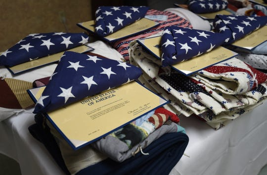 American flags and veterans quilts sit folded on a table at Gassville Therapy & Living. U.S. Rep. Rick Crawford presented the flags and quilts to nine veterans at the facility Friday.